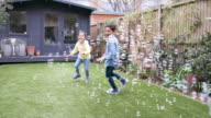 istock Children laughing and chasing bubbles in the garden 1161240984