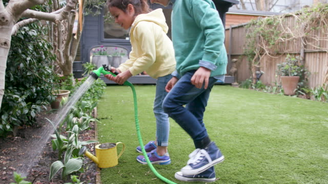 Children laughing together while watering the garden