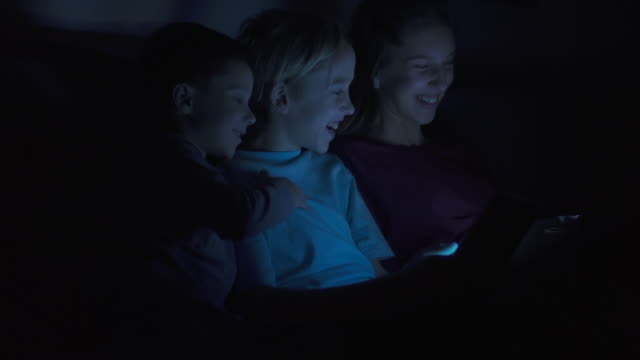 Children laughing while sitting on bed using gadgets with dim light video