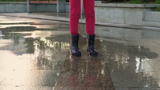 Children legs in rubber boots jump into puddle on granite sidewalk spray scatter video