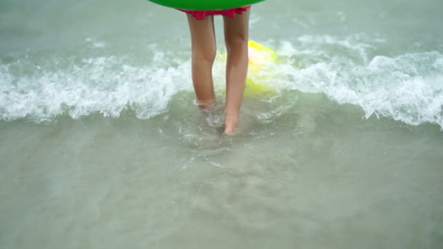 POV , children legs walking into sea with buoy