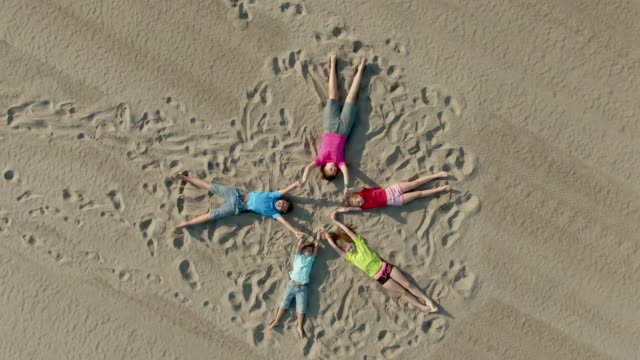 Children lie on the sand in the shape of a star and wave hands - video