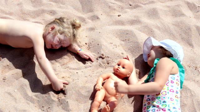 Children lie on the sandy beach. Sharm El Sheikh. Egypt. Children lie on the sandy beach of the red sea. Egypt. doll stock videos & royalty-free footage
