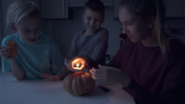 Children lightning a candle and put it in pumpkin video