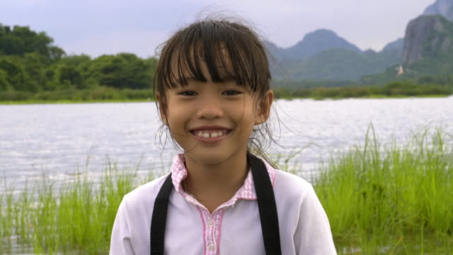 Children little cute asian girl 7 years old smile and enjoying making photo traveling in nature Mountains and rivers in evening.  Adventure holidays