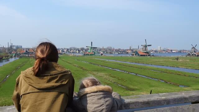 children looking at wind mills in Zaanse Schans, Netherlands children looking at wind mills in Zaanse Schans, Netherlands dutch architecture stock videos & royalty-free footage