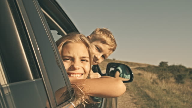 Children looking out car window, smiling at camera video