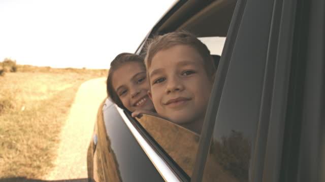 Enfants regardant dehors la fenêtre de la voiture - Vidéo