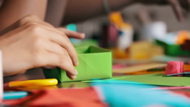 children make crafts out of paper at the table, handmade - feltro video stock e b–roll