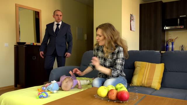 子供の乳母は、予想外の赤ちゃんの父を返すときにソファの上に横たわってリラックス。静止三脚ショット。4K UHD ビデオクリップ。 ビデオ