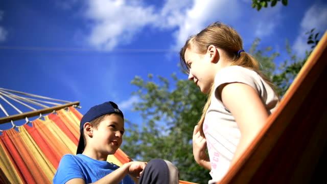 children on a hammock playing rock-paper-scissors, girl win, slow motion video