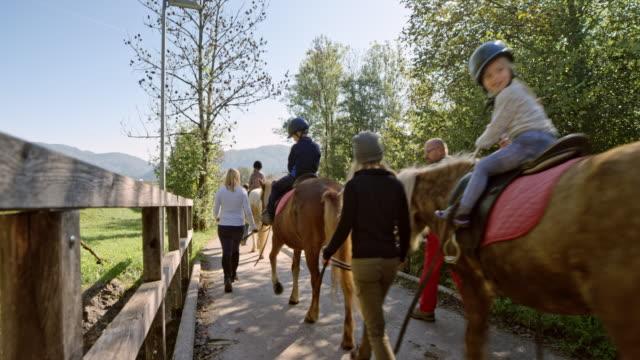 Children on horses walking across a small bridge in sunshine