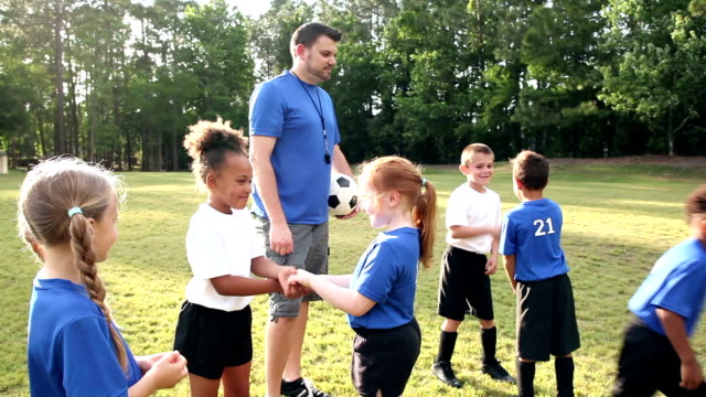 Children on soccer team shaking hands with opponents A coach and multi-ethnic group of children playing soccer. The boys and girls on opposite teams are showing good sportsmanship, shaking hands with their rivals. rivalry stock videos & royalty-free footage