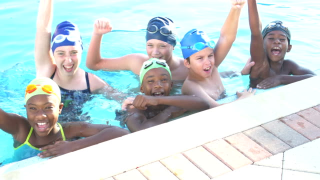 Children on swim team in pool, raise arms and cheer