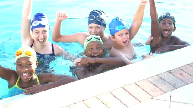 stockvideo's en b-roll-footage met kinderen op de zwemvereniging in zwembad, verhogen armen en juichen - competitie