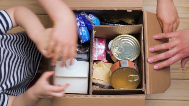 children opening a food delivery box at home, online ordering. grocery store delivery. box full of food in concept donation boxparcel. delivery during quarantine due to coronavirus covid-19 disease - голодный стоковые видео и кадры b-roll