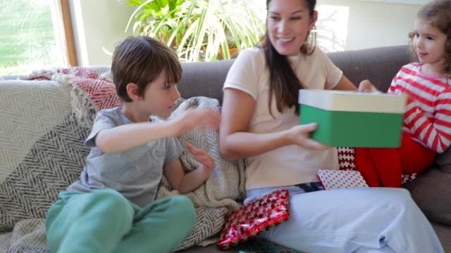 barn öppnar julklappar på soffa - christmas gift family bildbanksvideor och videomaterial från bakom kulisserna