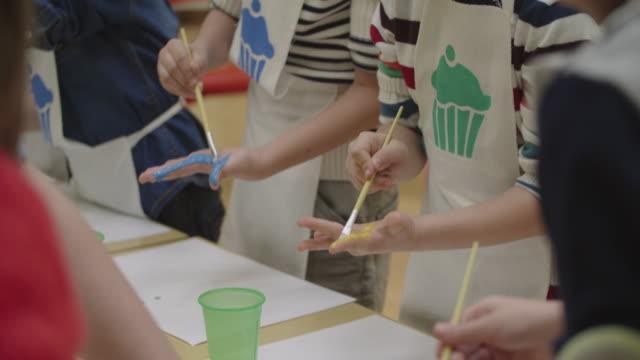 stockvideo's en b-roll-footage met 4k: kinderen hun handen met aquarellen schilderen - onherkenbaar persoon