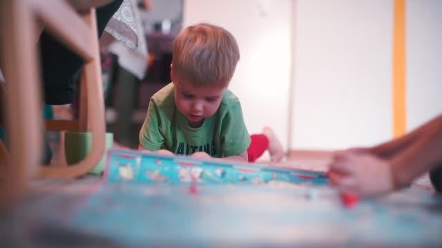 vídeos y material grabado en eventos de stock de los niños juegan un juego de mesa en el suelo. - tablón