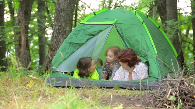 Children play in a green tent, set in a clearing in the forest video