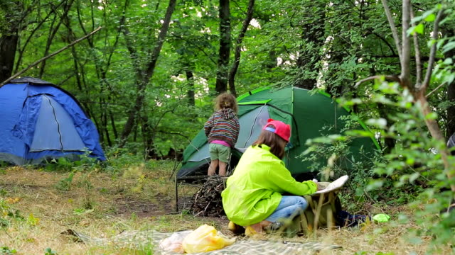 Children play in the clearing near the tents in the forest. video