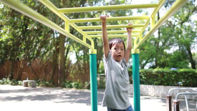 vídeos y material grabado en eventos de stock de los niños juegan en el parque - entrenamiento con pesas