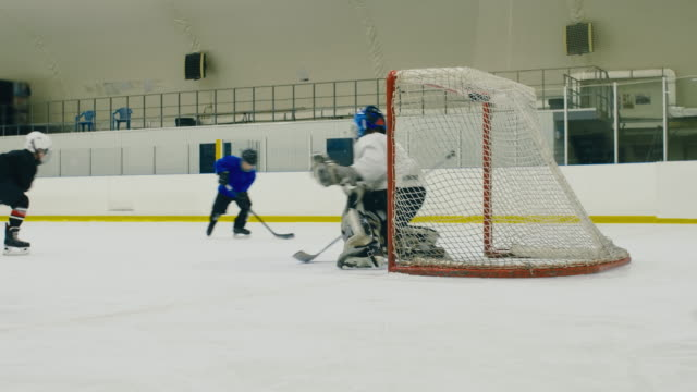 Children playing hockey Small ice hockey players passing the puck near goal post but shooting wide goal post stock videos & royalty-free footage