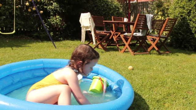 vídeos y material grabado en eventos de stock de los niños juegan en la piscina infantil - backyard pool