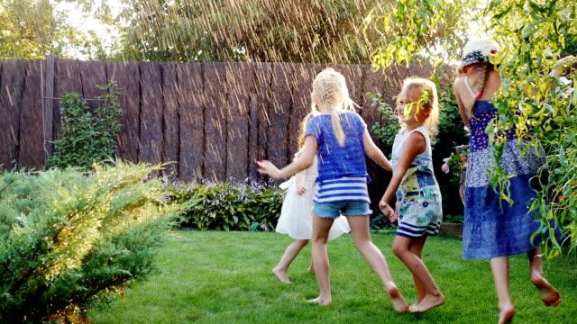 Children playing in the summer garden. Grupa children have fun under water jets or rain video
