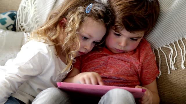 遊ぶ子供、デジタルタブレットを持っている ビデオ