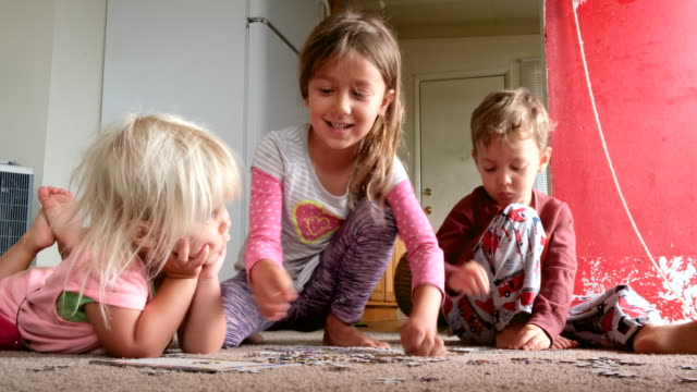 children playing on the floor solving a puzzle - puzzle video stock e b–roll