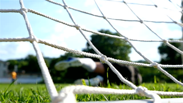 Children playing soccer game, camera behind the goal net video