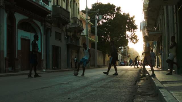 barn spelar fotboll i gamla havanna gränden - walking home sunset street bildbanksvideor och videomaterial från bakom kulisserna