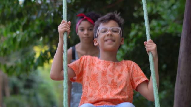 kinder spielen schaukel im öffentlichen park - schaukel stock-videos und b-roll-filmmaterial