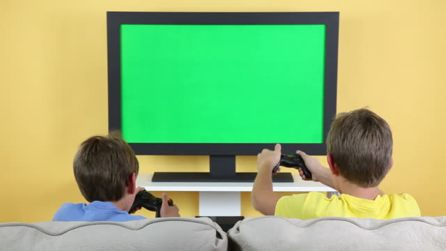 vídeos de stock e filmes b-roll de crianças jogando jogos de vídeo com a chave de croma-ecrã de televisão - tv e familia e ecrã