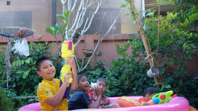 Children playing water gun together in kiddie's pool