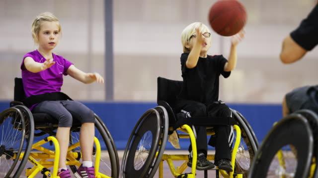 vídeos y material grabado en eventos de stock de niños jugando al básquetbol para silla de ruedas - deportes en silla de ruedas