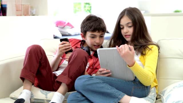 遊ぶ子供、デジタルタブレットと mp 3 プレーヤー - 兄弟点の映像素材/bロール