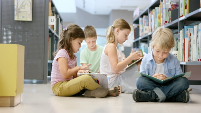 DS Children reading books on the floor of public library Medium dolly shot of four children reading books while they sit on the floor at the children section of the public library. elementary age stock videos & royalty-free footage