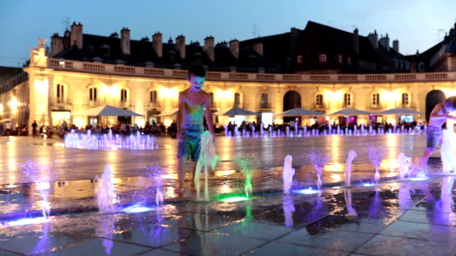 Children, refreshing on a very hot summer day, walking in fountain, playing with water at night, summertime