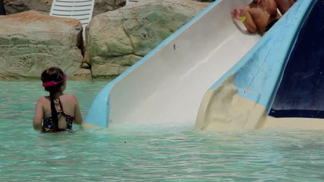 bambini in un ottovolante in piscina - brent video stock e b–roll