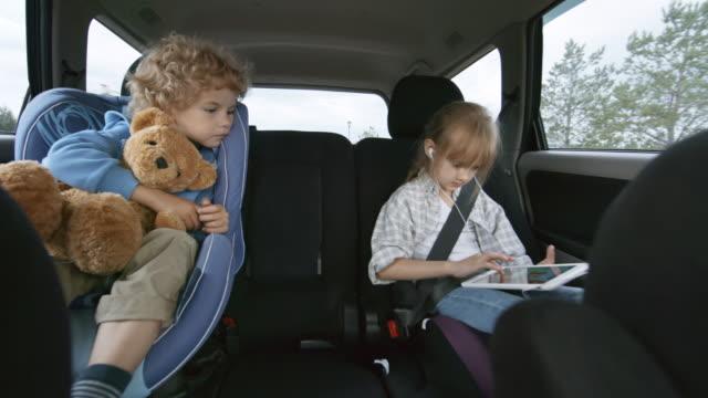 車の後部座席に乗る子供たち - 兄弟姉妹点の映像素材/bロール
