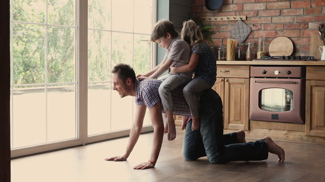 Children riding on daddy back playing together in kitchen