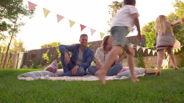 children run around parents as they sit on blanket in garden - happy holidays filmów i materiałów b-roll