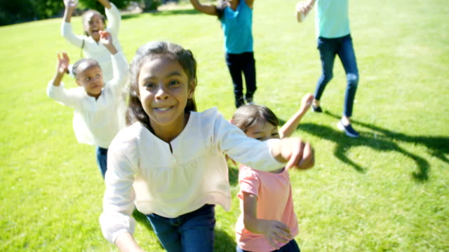 Children Running in Field Children running in a grassy field having fun and playing together. grass area stock videos & royalty-free footage