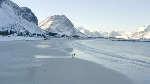 children running walking and having fun  on a winter polar beach Ramberg at the north of Norway