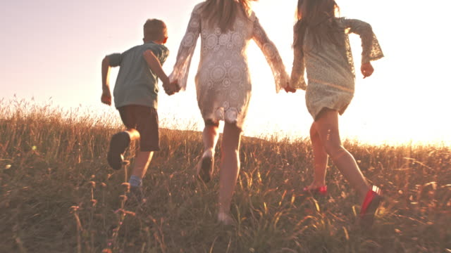 Children running with mother in nature, enjoying summer sunset video