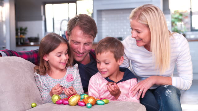 Children Sitting On Sofa With Parents Eating Easter Eggs video