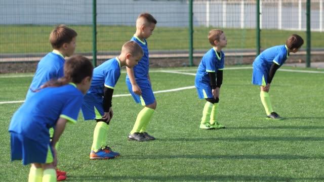 サッカー場でウォーミングアップする子供サッカーチーム - サッカークラブ点の映像素材/bロール