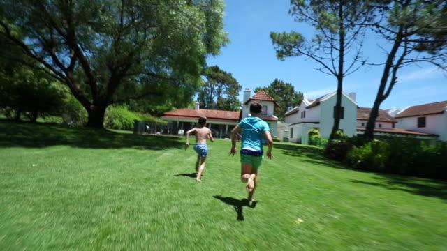 vídeos y material grabado en eventos de stock de niños corriendo fuera en el jardín de la casa del patio trasero y saltando en el agua de la piscina - backyard pool